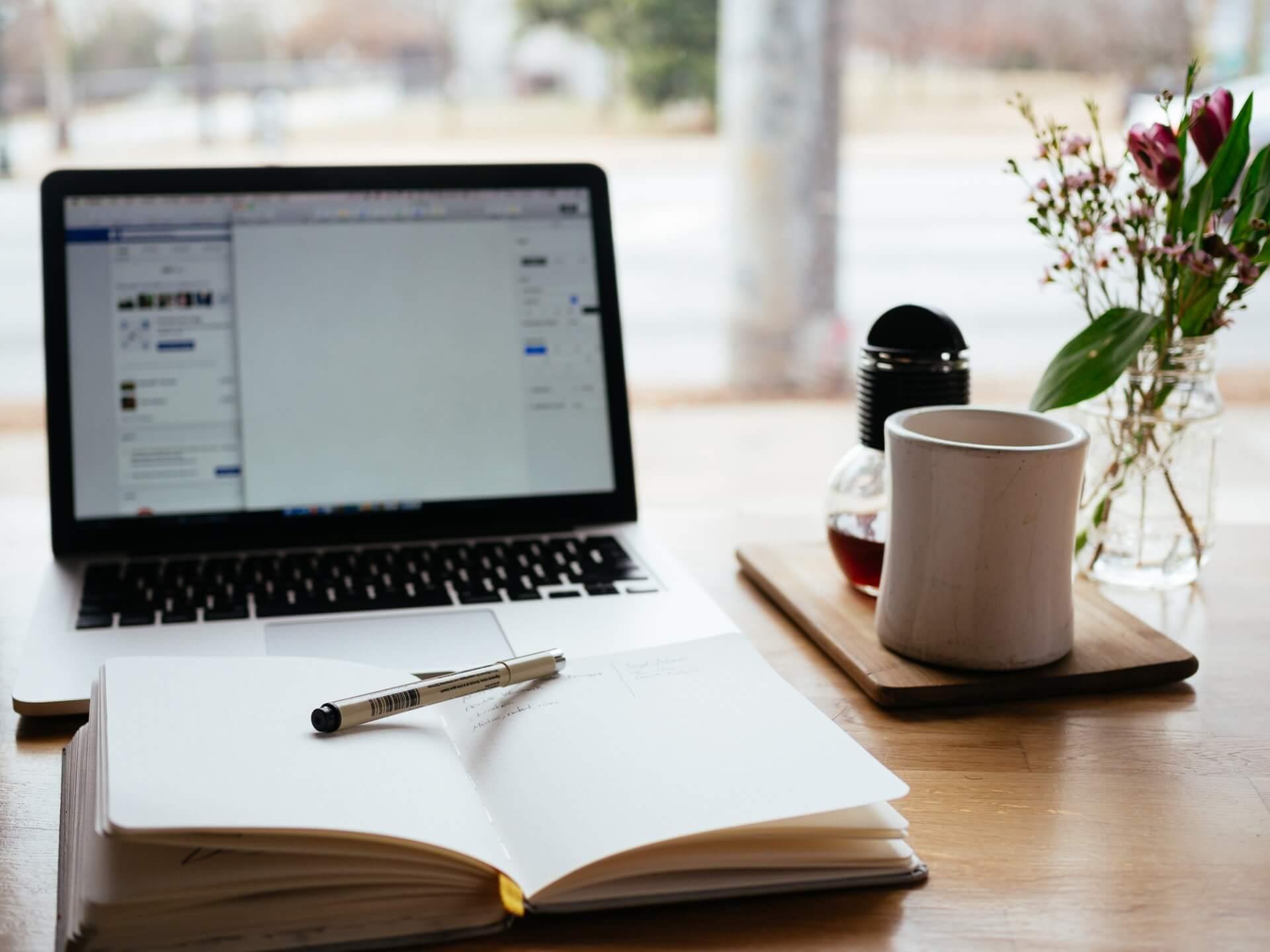Carnet de note ouvert devant un ordi pour écrire - Photo by Nick Morrison on Unsplash