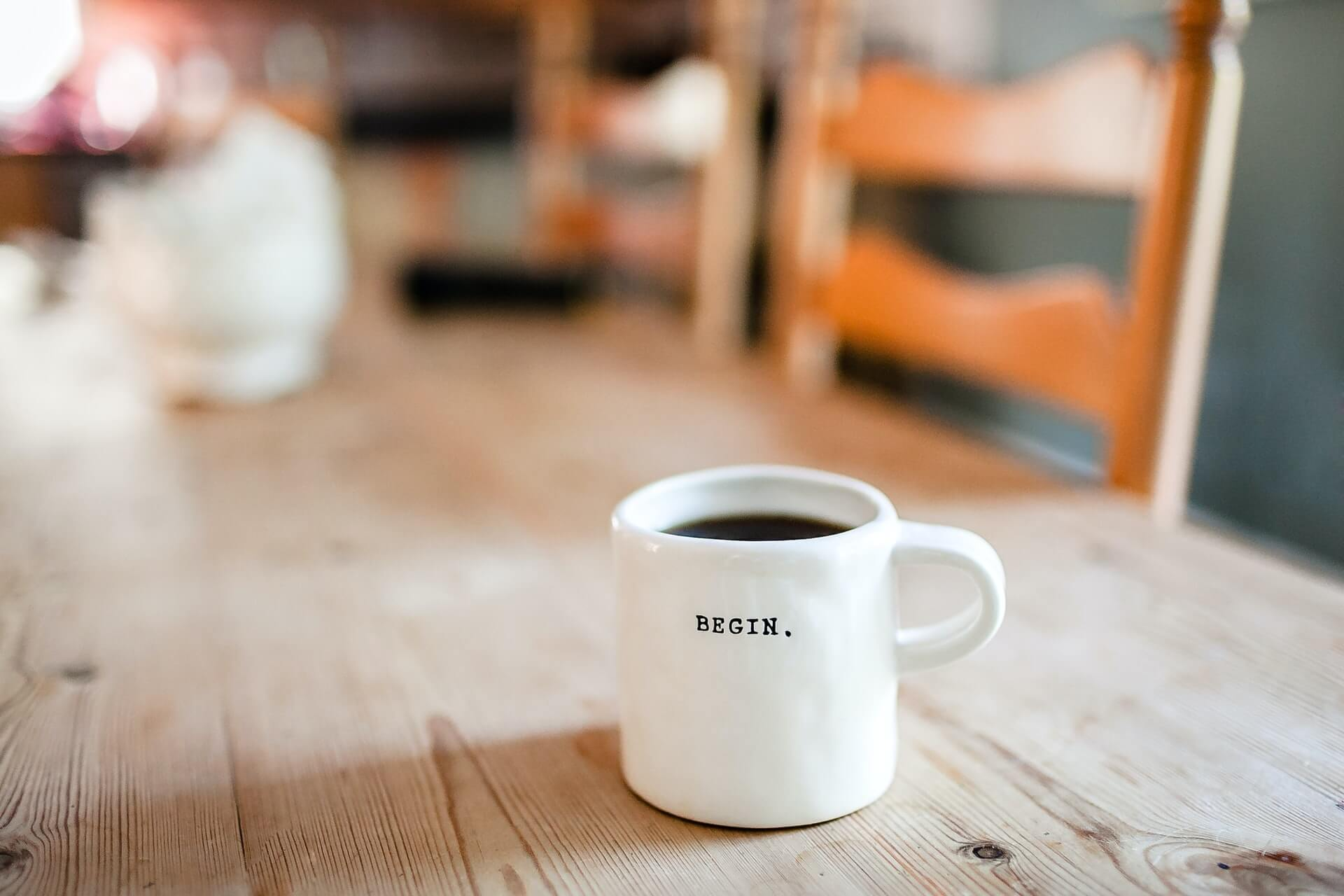 """Tasse avec message """"Begin"""" sur une table -Photo by Danielle MacInnes on Unsplash"""